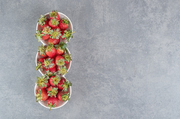 Leckere reife erdbeeren in weißen schalen. foto in hoher qualität