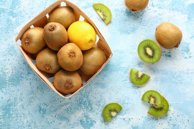 Leckere reife kiwi und zitrone im karton auf farbigem hintergrund