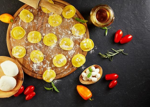 Leckere rohe ravioli mit mehl, kirschtomaten, sonnenblumenöl und basilikum auf dunkler draufsicht