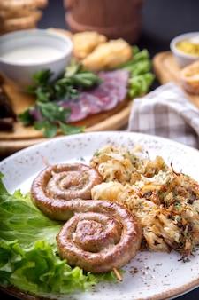 Leckere runde bratwürste auf holzspießen mit gebratenem sauerkraut. deutsches essen