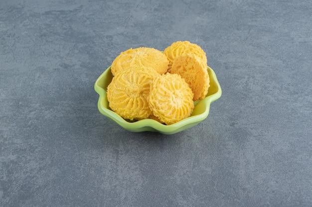 Leckere runde kekse in grüner schüssel.
