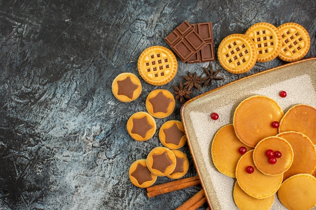 Leckere runde pfannkuchen mit leckeren süßigkeiten auf grau