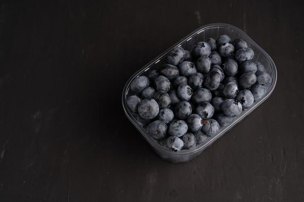 Leckere saftige rohe blaubeeren in einem plastikbehälter auf einem schwarzen dunklen hintergrund. verpackung für beeren in einem supermarkt in den verkaufsregalen.