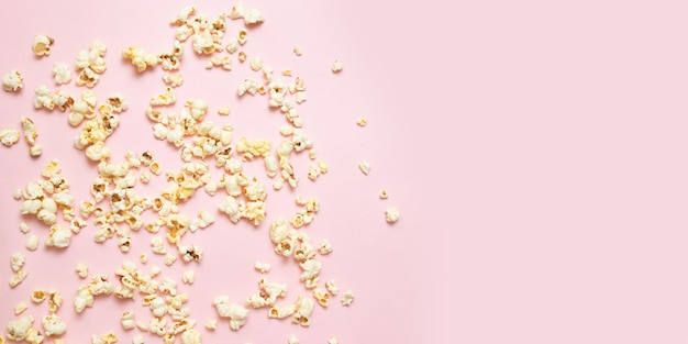 Leckere salzige oder süße popcorngrenze auf rosa hintergrund mit kopienraum. film schauen, kino, konzept.