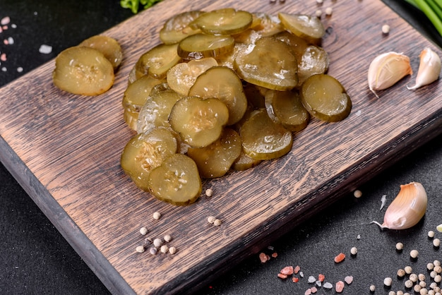 Leckere salzige würzige eingelegte gurke, die mit ringen auf einem hölzernen schneidebrett auf einem dunklen betonhintergrund geschnitten wird