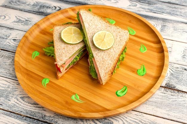 Leckere sandwiches auf holzschreibtisch und grau