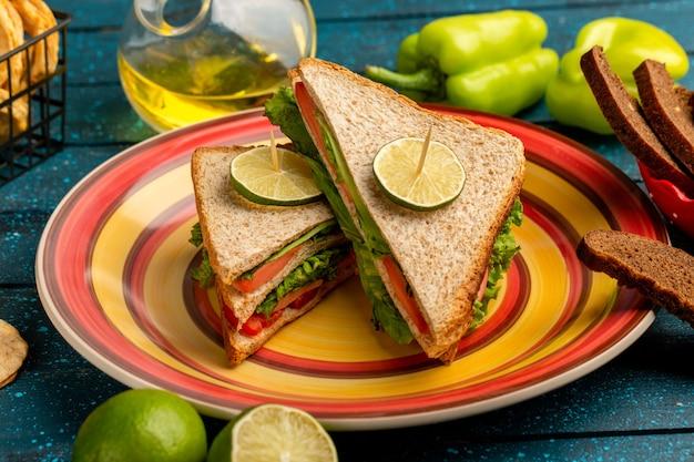 Leckere sandwiches mit grünen salattomaten zusammen mit grünem paprikabrot und zitrone auf blau