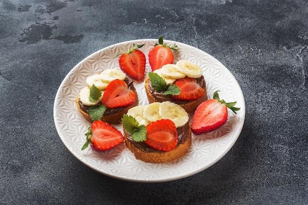 Leckere sandwiches mit schokoladennougat, erdbeere und banane.