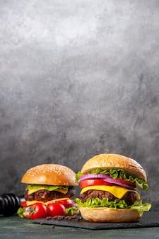 Leckere sandwiches pfeffer und tomaten auf schwarzem brett auf dunkler mischfarboberfläche