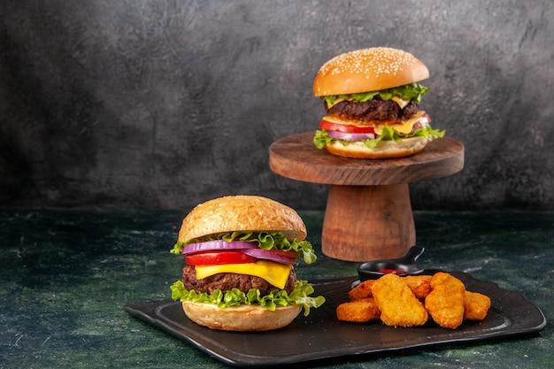 Leckere sandwiches pommes chicken nuggets auf schwarzem schneidebrett pommes frites pfeffer auf dunkler mischfarbe unscharfer oberfläche
