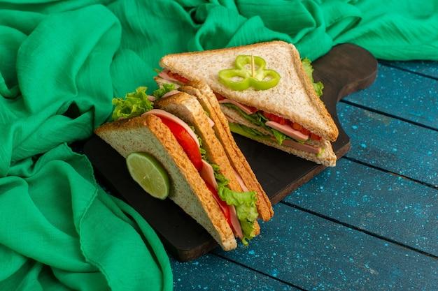 Leckere sandwiches zusammen mit grünem taschentuch auf blau