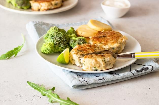 Leckere schnitzel (fisch oder fleisch) mit brokkoli, kartoffeln und sauce auf einem teller.