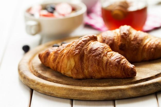 Leckere schöne croissants auf holzbrett. traditionelles kontinentales frühstück. granola mit früchten und honig auf hintergrund.