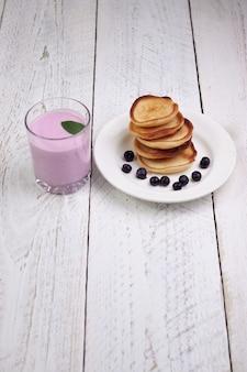 Leckere schöne pfannkuchen mit blaubeeren und blaubeerjoghurt auf einem hellen holztisch mit minzblättern.