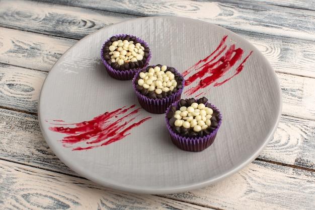 Leckere schokoladen-brownies mit schokoladenstückchen in lila platte auf rustikalem grau