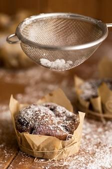Leckere schokoladenmuffins in puderzucker auf dem tisch