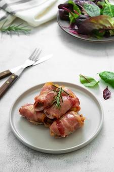 Leckere schweine in decken, in speck gewickeltes fleisch, hausgemachte gekochte fleischbissen. helles essensfoto.