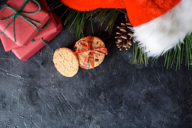 Leckere shortbread-kekse mit schokoladenstücken, mit rotem band, einem fichtenzweig, santa's hat, einem shortie. weihnachtskomposition