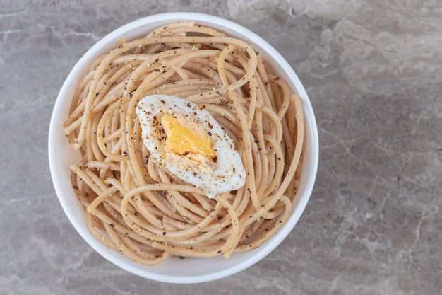 Leckere spaghetti mit ei in weißer schüssel.