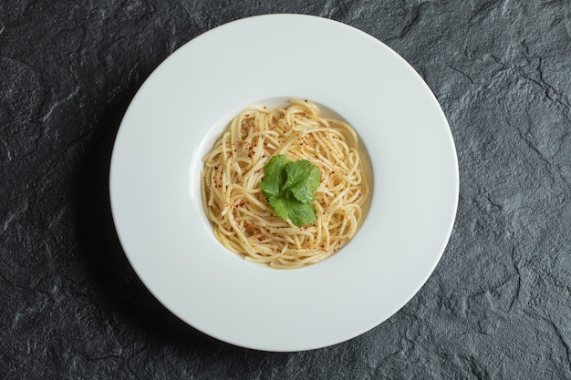 Leckere spaghetti mit gemüse auf einem weißen teller.
