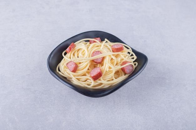 Leckere spaghetti mit geschnittenen würstchen in schwarzer schüssel.