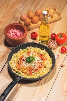 Leckere spaghetti mit tomatensauce und fleisch in der pfanne auf holztisch.