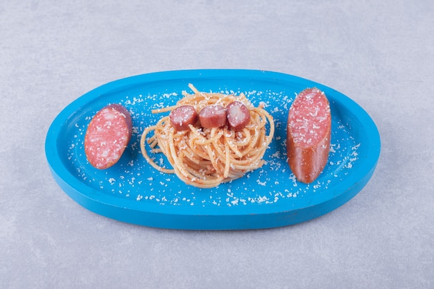 Leckere spaghetti mit würstchen auf blauem teller.
