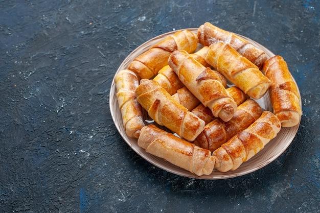 Leckere süße armreifen mit füllung in teller auf dunklem schreibtisch, süßer kekskuchen backen gebäck