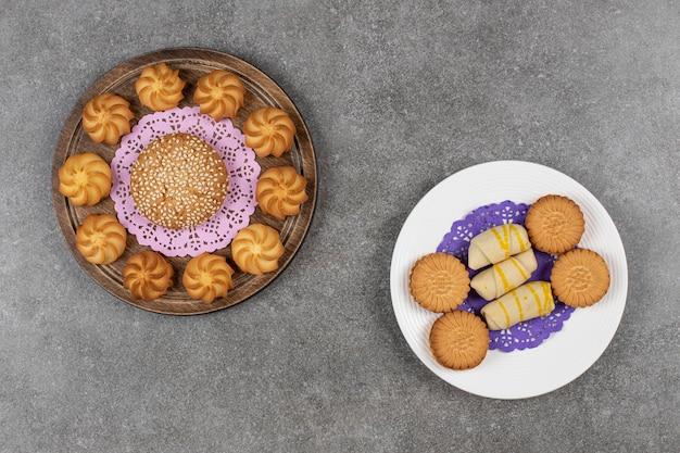 Leckere süße kekse und teller mit keksen auf marmoroberfläche.