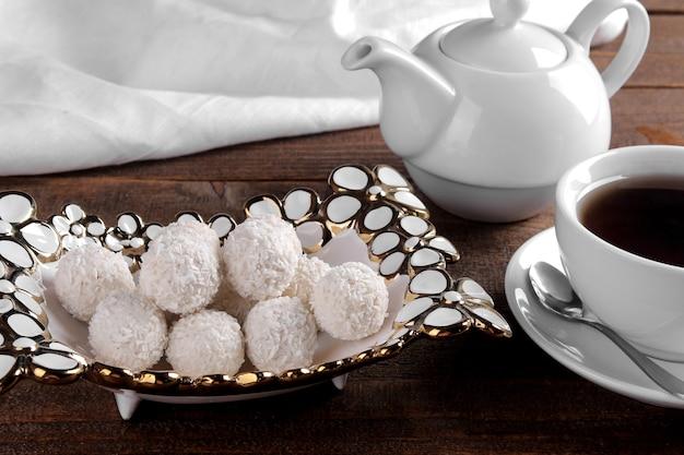 Leckere süße kokosbonbons in einer vase mit tee auf einem braunen holztisch.