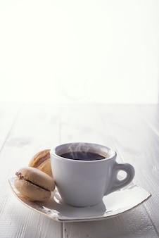 Leckere süße macarons und kaffeetasse. makronen auf weißem hölzernem hintergrund. platz kopieren