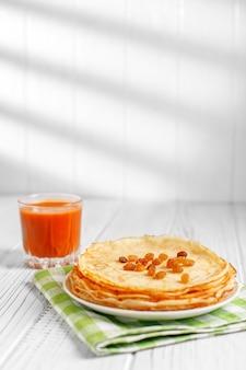 Leckere süße pfannkuchen mit rosinen und karottensaft.