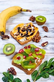 Leckere süße sandwiches mit bananen, nüssen und schokolade, auf holztisch