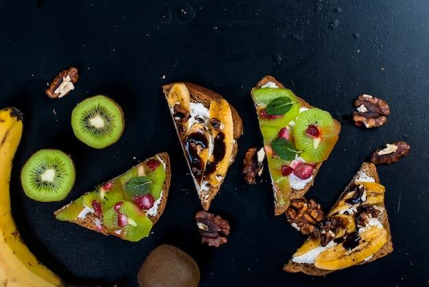 Leckere süße sandwiches mit bananen, nüssen und schokolade, kiwi, erdbeeren und minze auf schwarzem hintergrund