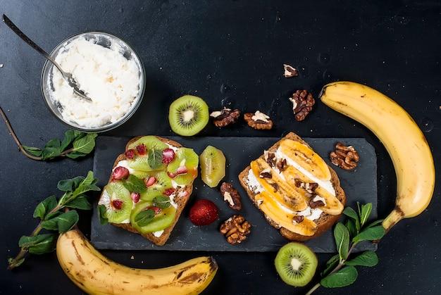 Leckere süße sandwiches mit bananen, nüssen und schokolade, kiwi, erdbeeren und minze