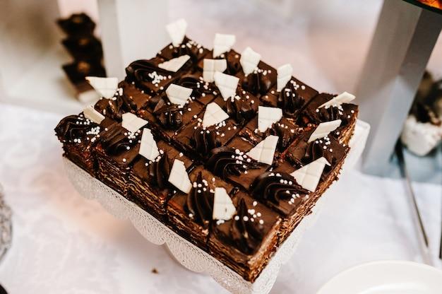 Leckere süße schokoladen- und vanillekuchen sowie rosa, pastellfarbene, beige makronen