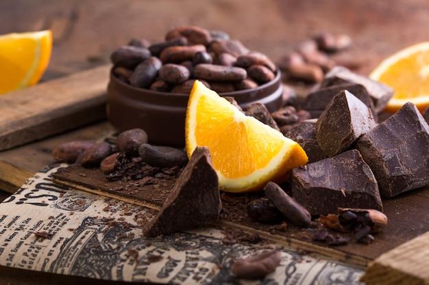 Leckere süßigkeiten, pralinen, kakaobohnen und orangenscheiben. draufsicht flach legen gruppenobjekte