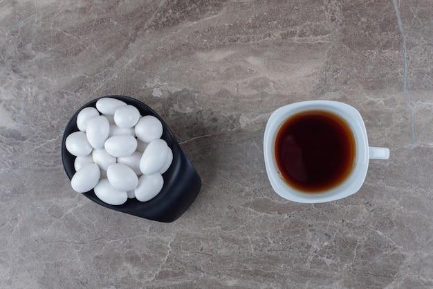 Leckere süßigkeiten und eine tasse tee auf der marmoroberfläche