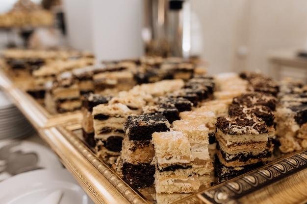 Leckere süßigkeiten werden auf goldtablett serviert