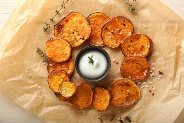 Leckere süßkartoffelchips und sauce auf pergament