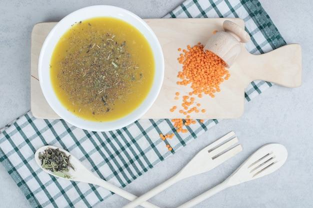 Leckere suppe mit linse und löffel auf tischdecke
