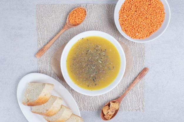 Leckere suppe mit linsen und löffel auf tischdecke
