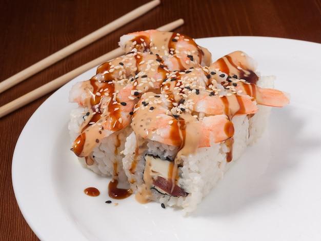 Leckere sushi-rolle mit riesengarnele auf einem weißen teller