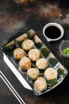 Leckere sushi-rollen in einwegboxen auf altem, dunklem rustikal