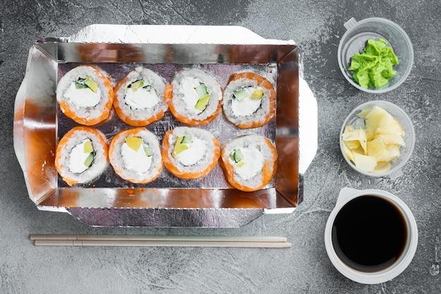 Leckere sushi-rollen in einwegboxen auf grauem stein