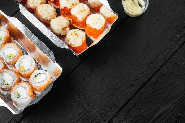 Leckere sushi-rollen in einwegboxen auf schwarzem holztisch