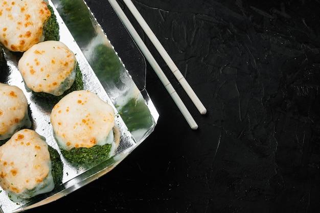 Leckere sushi-rollen in einwegboxen auf schwarzem stein