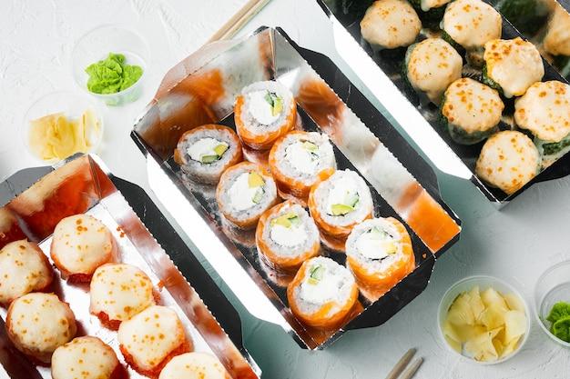 Leckere sushi-rollen in einwegboxen auf weißem stein