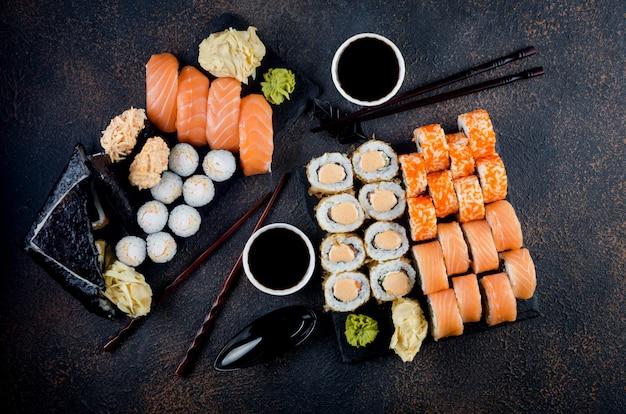 Leckere sushi-rollen mit saucen, essstäbchen und ingwer auf dem tisch. lieferservice japanisches essen