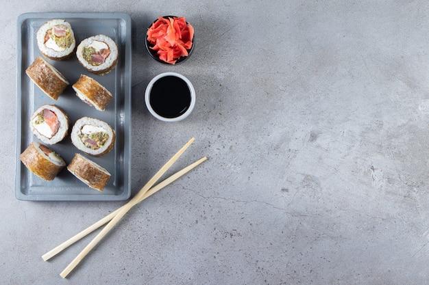 Leckere sushi-rollen mit thunfisch und eingelegtem ingwer auf dunklem brett.